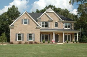 A two-story brick house with a grassy lawn and a red real estate sign out front.
