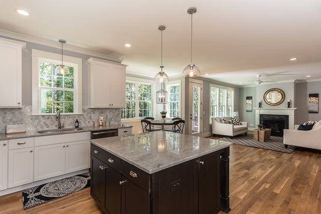 A gourmet kitchen with center island, hardwood floors, and open floor plan to the living room.