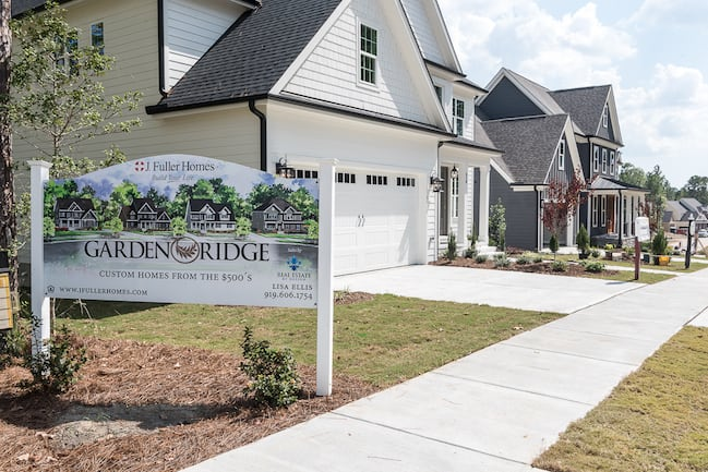 A homebuilder sign on a lawn in a new home neighborhood.